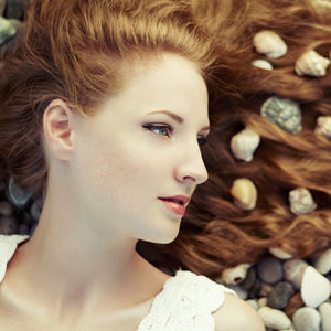 Beautiful young woman with unusual hairstyle on beach. Fashion photo